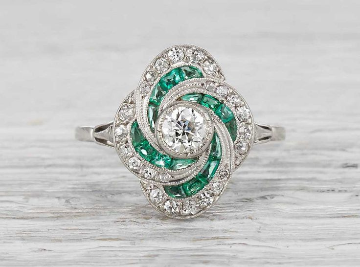 Antique Art Deco ring made in platinum and centered with an approximate .35 carat old European cut diamond. Accented with emeralds and single cut diamonds. Circa 1925. This elegant setting has a lot o
