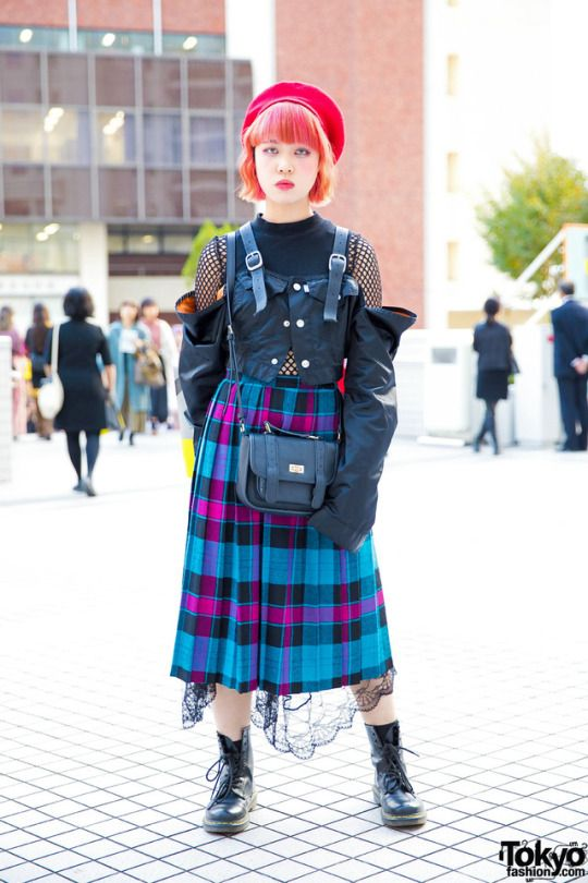 15-year-old Japanese high school student Sagumo on the street in Tokyo wearing a jacket by the Harajuku streetwear brand MYOB NYC over a fishnet top, a vintage pleated skirt with black lace embellishment, Dr. Martens boots, and an H&M bag. Full Look