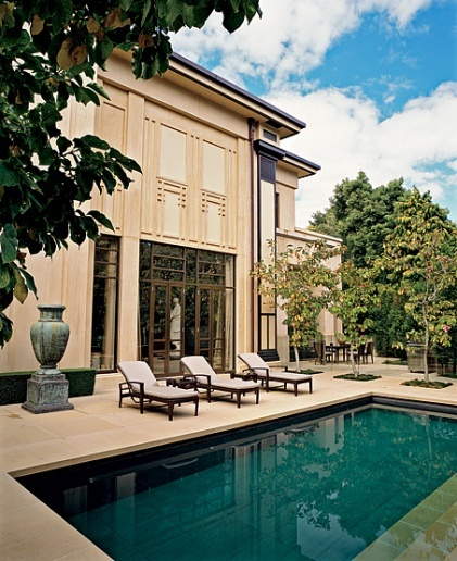 Landscape architect Rick Eckersley lined the terrace with magnolias. The sandblasted-plaster façade is decorated with an embossed geometric pattern that evokes the   Architecture by Ivo Krivanek/Interior Design by Hendrix Allardyce/Landscape Architecture by Eckersley Stafford Design