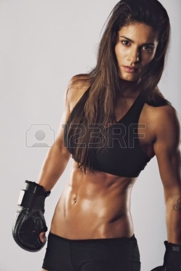 Female kickboxing fighter with an intense look. Muscular woman with boxing gloves looking at camera against grey background photo