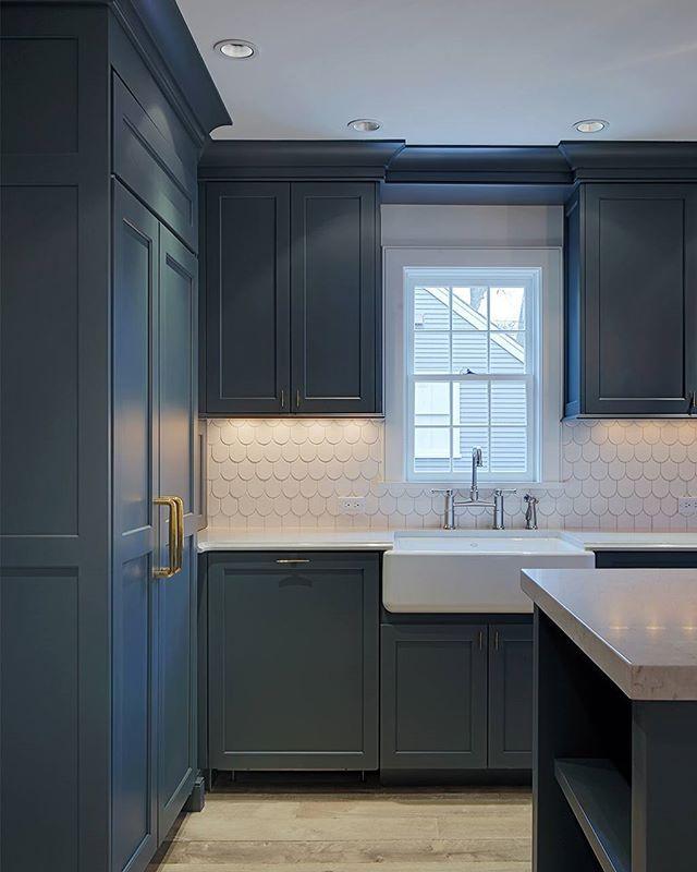 We See Dark Blue Cabinets Gold Handles And A Shingle Backsplash