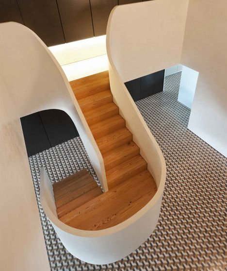 Of the innumerable ways to create a functional focal point in your home, a sculptural staircase might be the most visually stunning. This example from a duplex in Braga, Portugal was designed and built by Correia/Ragazzi Arquitectos for a family's duplex.