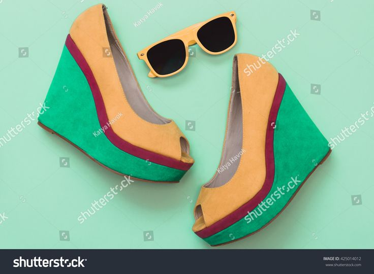 Flat lay fashion set: yellow and green shoes with sunglasses on mint background. Top view.
