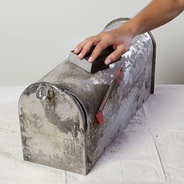 Sanding a metal mailbox in preparation for primer