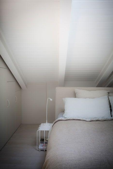 Tonalità chiare, dal bianco al beige, per la zona notte. Il letto è di Flexform, il comodino è di Desalto