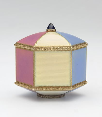 A hexagonal gold box by Fabergé, in cream, pale blue and pink guilloché enamel with convex cover set with cabochon sapphire at centre and base mounted with chased foot rim. Mounts similarly chased with foliage. Provenance: Gift of George V, 1 January 1929.