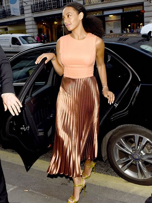 Solange Knowles's Kiehl's Pioneers By Nature Party Peach Top, Etienne Aigner Metallic Accordion Skirt, and Neon Green Sandals