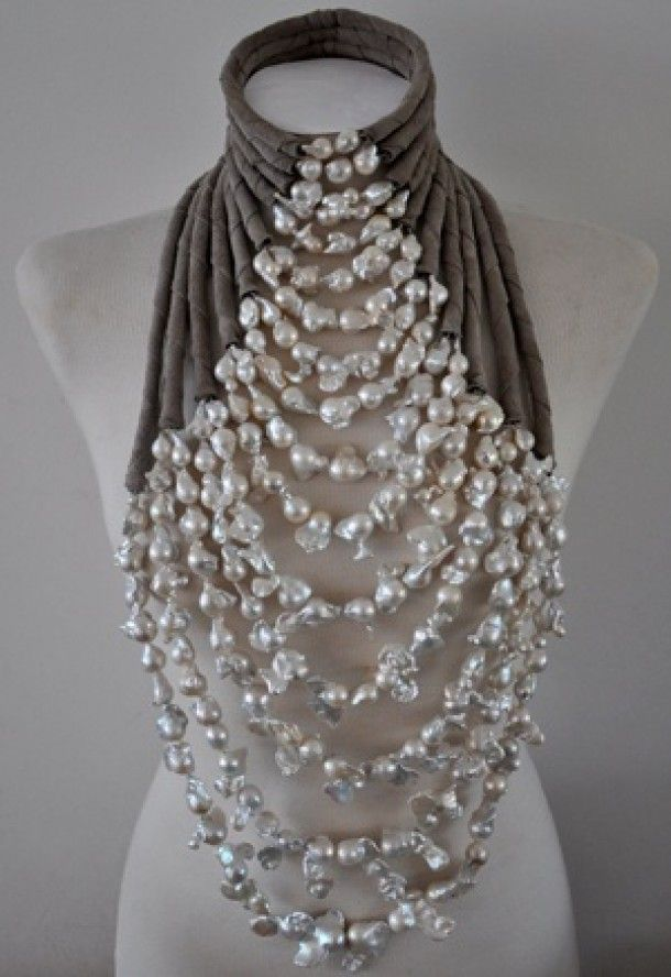 Huge naturally shaped beads in layers, the tops of each stand wrapped I fabric to form a high-neck collar