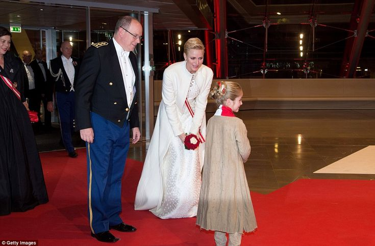 The Princess kneels down to talk to a young girl at the gala on the National Day of Monaco, also known as The Sovereign Prince's Day