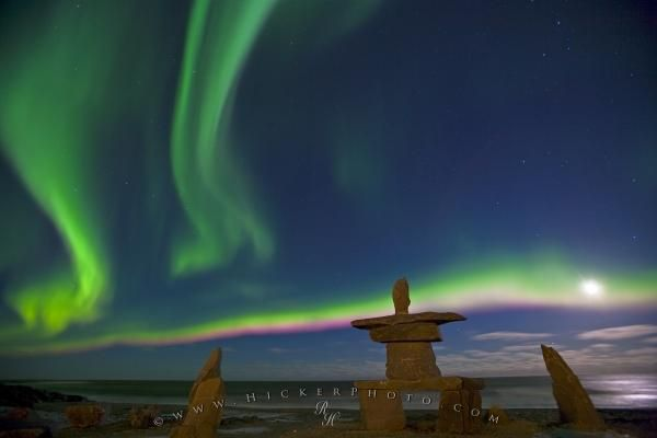 Photo of Northern Lights dancing next to a full moon over an inukshuk in Hudson Bay, Canada.
