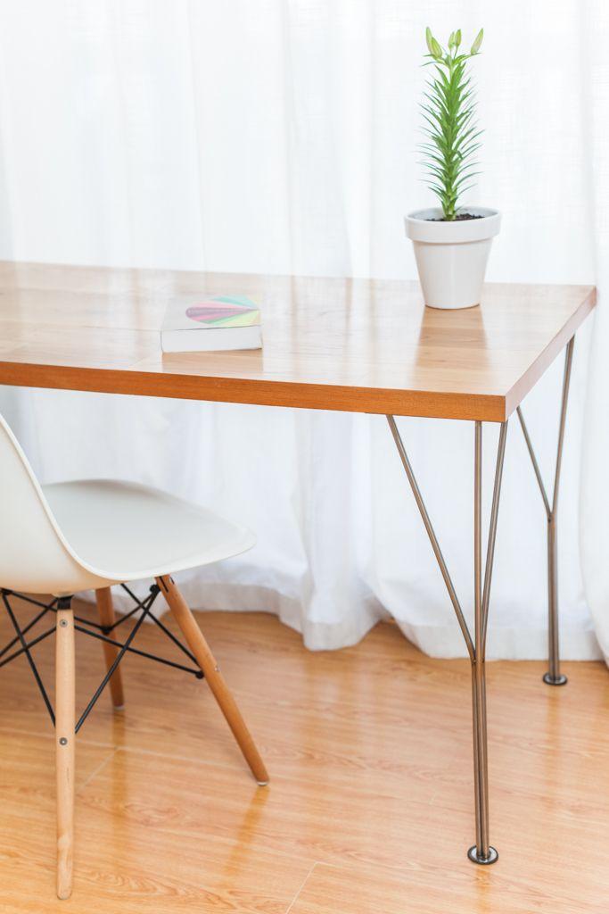 Detalle de mesa con tapa de roble y patas de acero inoxidable curvado. Silla Eiffel.