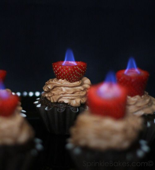 Chocolate cupcakes with flaming strawberries.