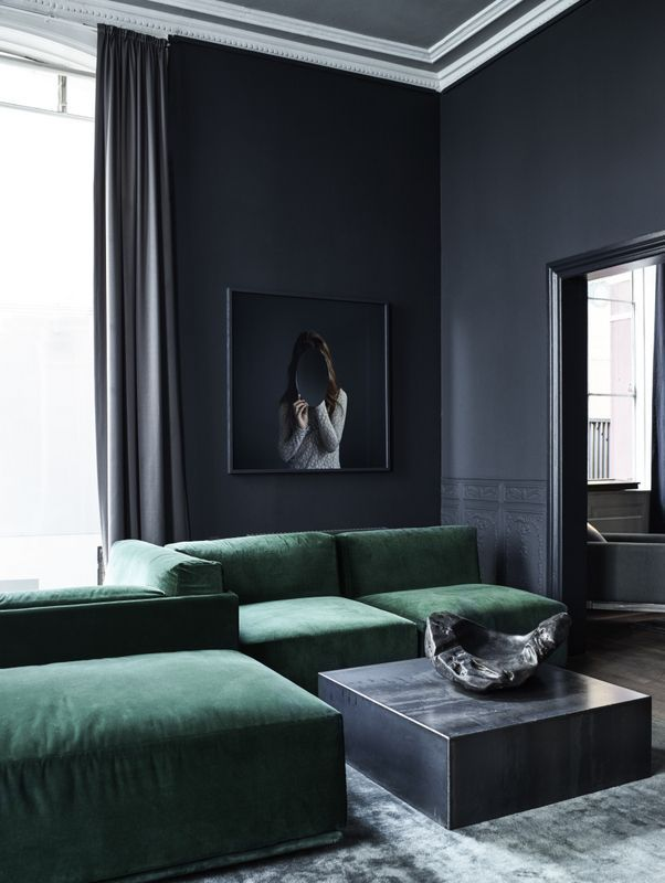 Elegant and dark living room with an amazing emerald green sofa by Rue Verte.