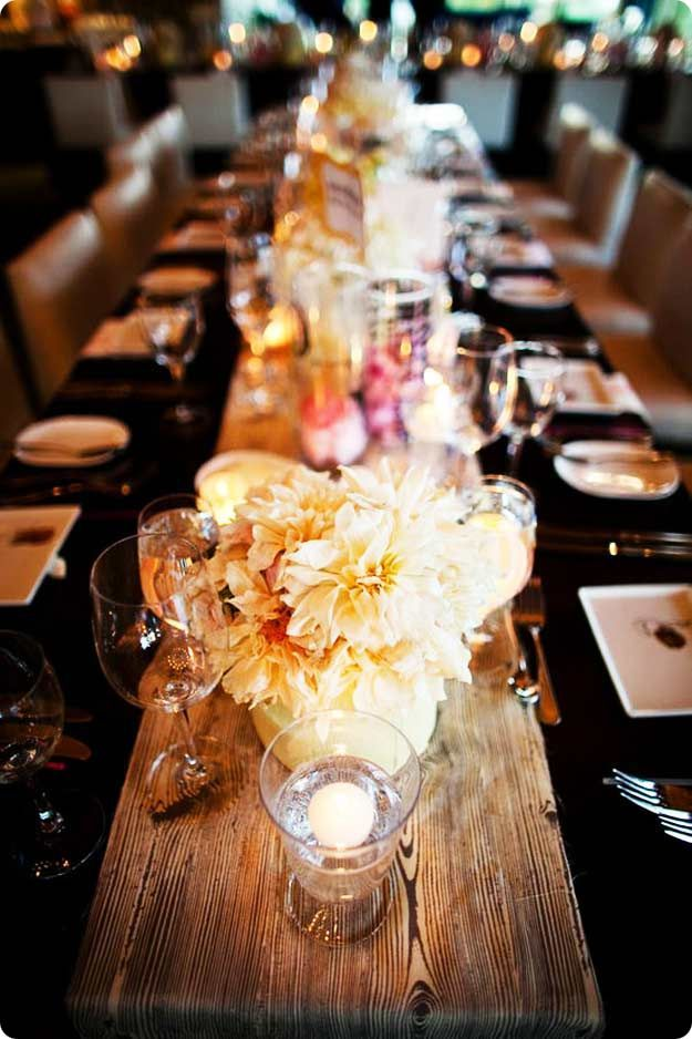 use a rustic wood plank as a runner for simple flowers and glowing candles // fall entertaining