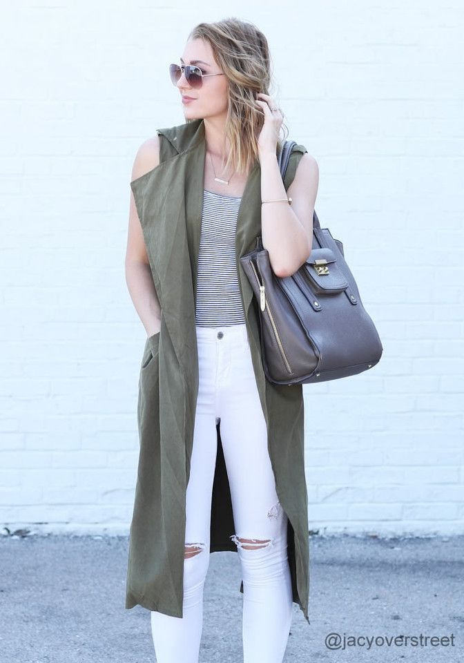 Front view of model in army green sleeveless trench coat
