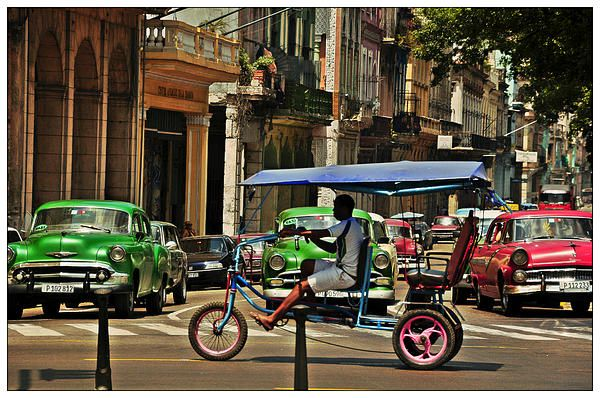 Havana traffic with some oldtimers and bici taxi.