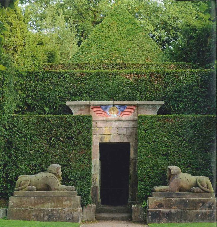 Sphinxes guard the entrance to the tunnel where a statue of the baboon-headed Thoth resides, with a yew-tree pyramid as their backdrop in the gardens at #BiddulphGrange #staffordshire