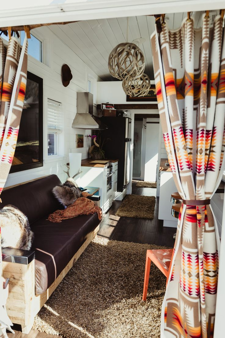 Pendleton Wool Blankets have been made into custom curtains. A beautiful couch created out of reclaimed barn wood and bison leather gives the Tiny Home just the right amount of Western flair. More custom touches like the globe antler chandeliers and stools from the famous Shoshone Malt Shop, bring Wyoming's history to life.