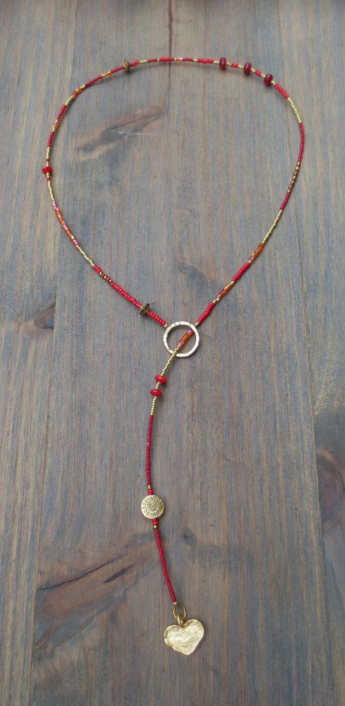 Lariat in red, orange and gold Miyuki seedbeads, red coral beads, gold plated disc bead with gold plated hammered heart charm. *Each lariat comes with our clip bead