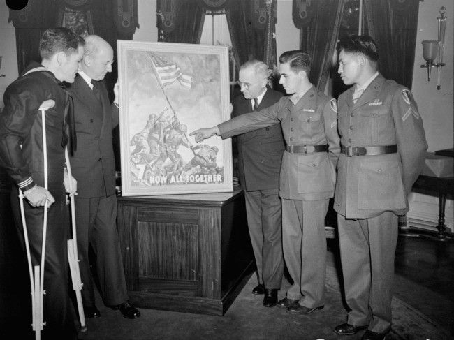 With the three survivors of the famed Mt. Suribachi flag-raising incident as his guests, President Truman gets the first of the new 7th war loan posters, based on Joe Rosenthal's epic Iwo Jima photograph, at the White House, April 20, 1945. Left to right: John H. Bradley, of Appleton, Wisconsin; Secretary of the Treasury Henry Morgenthau, obscured; President Truman; Pfc. Rene A. Gagnon of Manchester, N.H.; Pfc. Ira H. Hayes, Bapchule, Az.