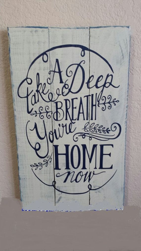 Take a Deep Breathe Youre Home Now pallet wood sign measures 10x17 and is painted a cream color with dark blue lettering with the Saying Take a Deep Breath Youre Home Now. This sign is sanded to give a distressed, shabby chic look. This sign comes ready to hang and the back is unfinished.