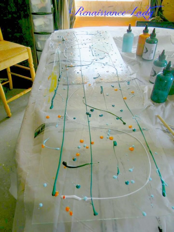 She lays out a large pane of glass, drips spots of colored gel, and wait until you see the final step!