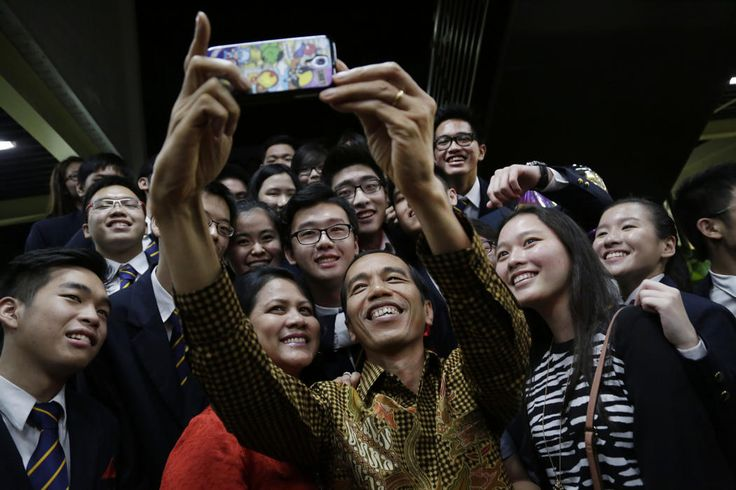 """Indonesian President Joko Widodo, popularly known as """"Jokowi"""", center, and his wife Iriana, center left, helps a student graduate take a selfie with a smartphone after attending a graduation ceremony for the International Baccalaureate Diploma Programme of his son Kaesang Pangarep, top right, at the Anglo Chinese School (International), in Singapore, Friday, Nov. 21, 2014. Jokowi flew to Singapore to attend the graduation of his youngest son Kaesang Pangarep. (AP Photo/Wong Maye-E)"""