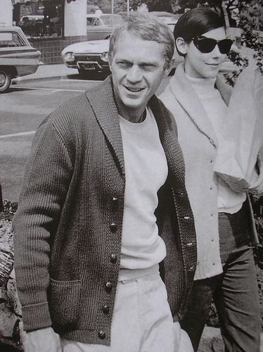 Steve McQueen casual style; shawl collar cardigan with leather buttons, white crewneck sweatshirt, stone grey trousers