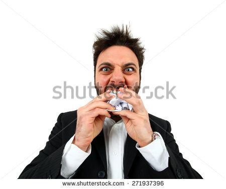 Young angry businessman while eating balled paper on white background.