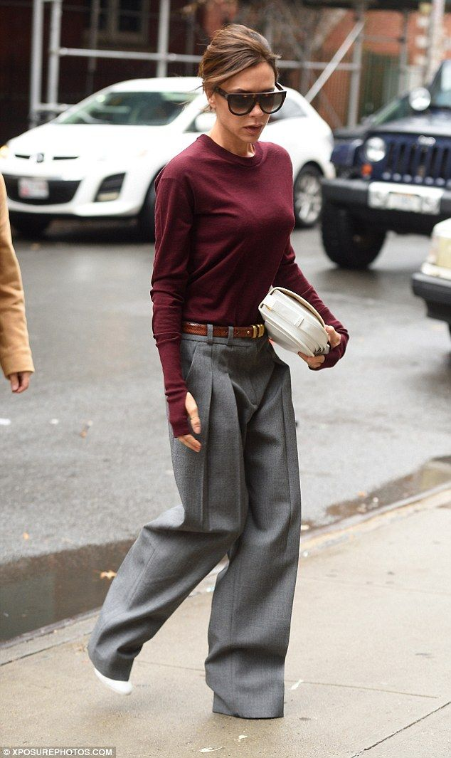 Victoria Beckham wearing a burgundy jumper and grey baggy trousers from her own collection.