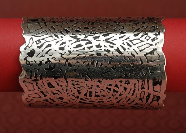 Szeroka metalowa bransoleta w kolorze srebrnym.