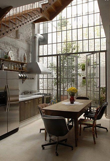 Beautiful Conservatory Kitchen and Dining Space   Organic and industrial textures combine to create a cozy ambience