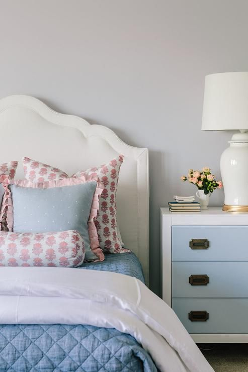 A White Fabric Wrapped Bed Dressed In White And Blue Bedding Topped With Blue And Pink Pillows Sits Against Blue Nightstands Blue And Grey Bedding Blue Bedding