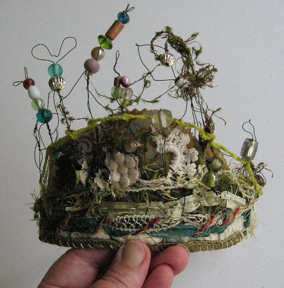 I have made this Fairie Crown in preparation for Midsummer. It is the Ragged Baggaraggs version of a Fairie Diadem, that with some pinning could be worn as a tiara if you had a mind to.  It is made of floral wire, free shaped by my hands, and sewn and woven with ribbon, chenilleand moss threads. There are numerous beads and doo-dads on the wire spires.  It is bendable, and is approxiametly 6 inches tall, and at this time is 7 inches wide. This would be perfect for a Fairie Bride on…