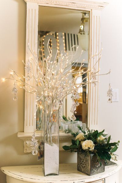 Foyer Table Vases : On an entryway table a vase filled with lighted branches