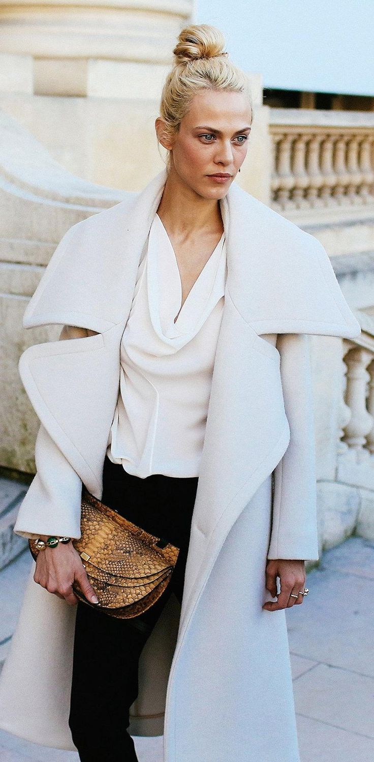Amyeline Valade in a white coat and python clutch