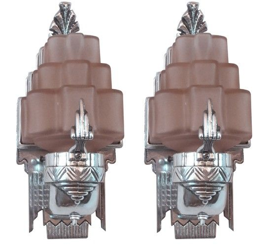 This pair of sexy american art deco sconces is from the constructed of highly polished aluminum and pink glass the sconces each have a pink glass shade