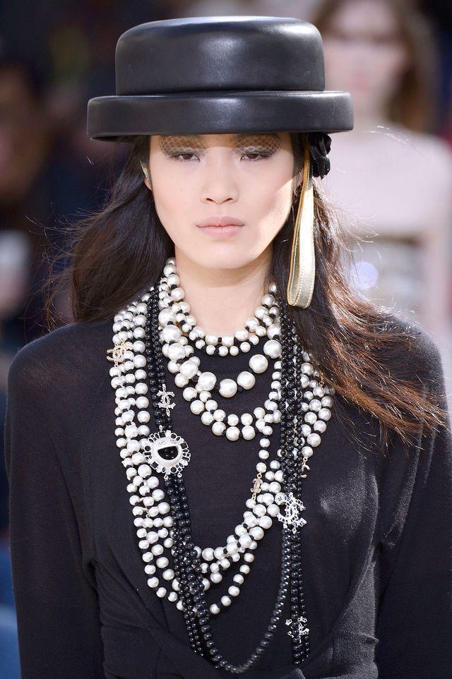 Défilé Chanel automne-hiver 2016-2017 - Chapeau rond en cuir -croisement du canotier de Coco et de la bombe d'équitation- et multiples sautoirs de perles.