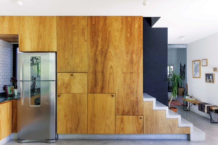 Cocina comedor integrados, con espacio debajo de la escalera revestido en fenólico de eucalipto.