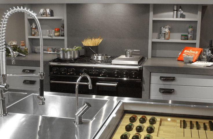 """Maatwerk keuken. Eiken houten fronten dekkend grijs gespoten met onze maatwerk """"Flinstone"""" handgrepen. Eiland in RVS doorlopend in de zijwanden met doorkijk glazen blad en maatwerk kruiden messenindeling."""