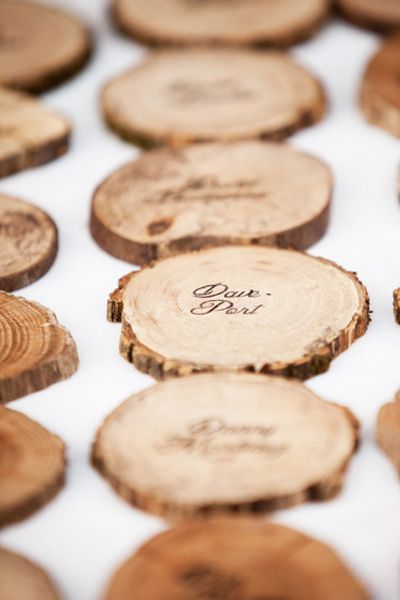 Seating assingments are stamped into the back of these rustic wood rounds. Guests can use them as a coaster for the couple's signature cocktail or bring them home for an original favor.