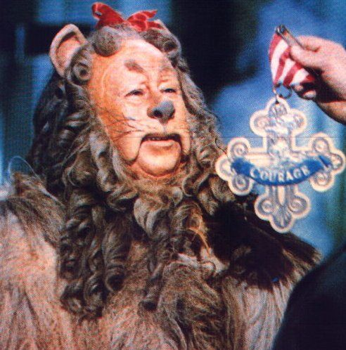 The Cowardly Lion recieves a badge of courage from the Wizard of Oz.
