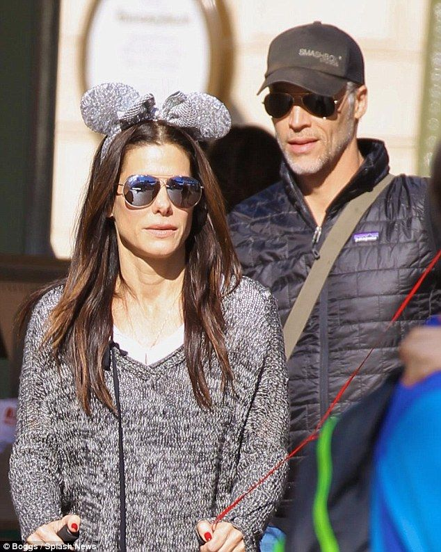 In sync at the happiest place on earth: Sandra Bullock and her boyfriend Bryan Randall were side by side when taking her two children Laila and Louis to Disneyland over the weekend