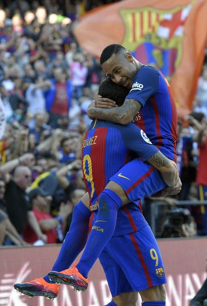 Barcelona's Uruguayan forward Luis Suarez (bottom) celebrates a goal with Barcelona's Brazilian forward Neymar during the Spanish league football match FC Barcelona vs RC Deportivo de la Coruna at the Camp Nou stadium in Barcelona on October 15, 2016. / AFP / LLUIS GENE