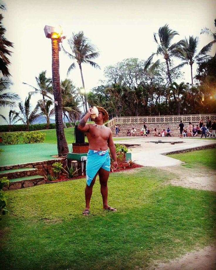 Hawaiian conch shell blower signalling the start of the luau activities at Paradise Cove. When in Hawaii it's a no brainer to do a luau experience,  and Paradise Cove in Oahu is a fun option. You'll be mesmerized by the performers. #travel #hawaii #luau #oahu
