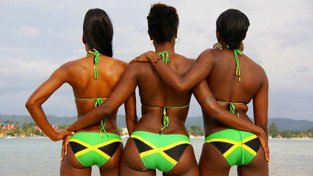 Three Jamaican girls wearing bikinis with the Jamaica flag design.