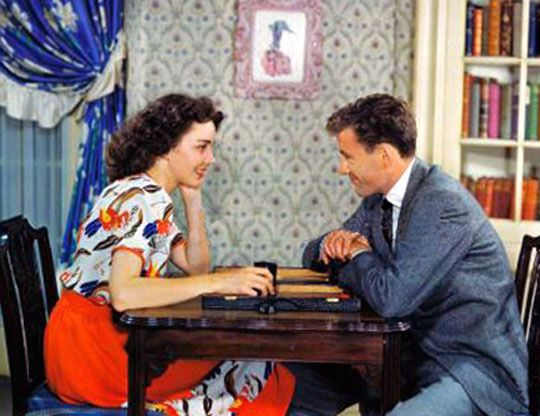 Husband and wife Jennifer Jones and Robert Walker play backgammon at home.                 Online backgammon > on.fb.me/1869cF3