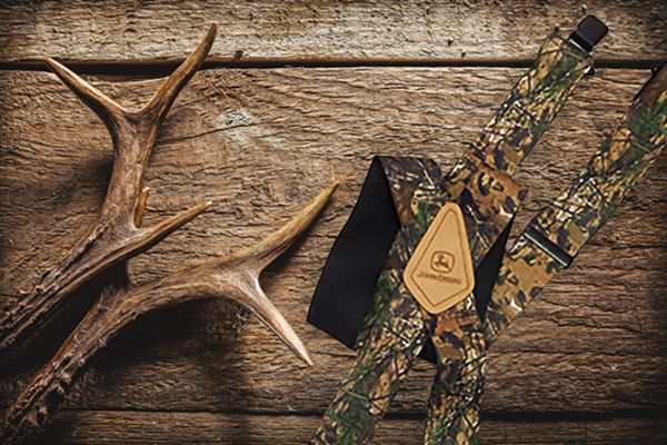 REALTREE XTRA Camo. 2 inch wide straps. 46 inches long. Black clips and adjusters. John Deere logo on natural leather back patch.