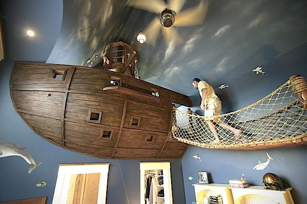 Habt ihr schon so ein gutes Kinderzimmer gesehen? Kuhl Design+Build haben dieses fantastische Piratenschiff in ein Kinderzimmer gebaut. Es schwebt praktisch unter der Decke und ist über eine Holzbrücke zu erreichen. Die Brücke allein ist ja schon super! Das Schiff scheint größer zu sein als man zunächst denkt. Es hat eine richtige Brücke mit einem Ausguck. Und einer Luke, durch die man sich an einem Seil in den darunterliegenden Wandschrank abseilen kann. Sollte ich jemals ein Haus bauen…
