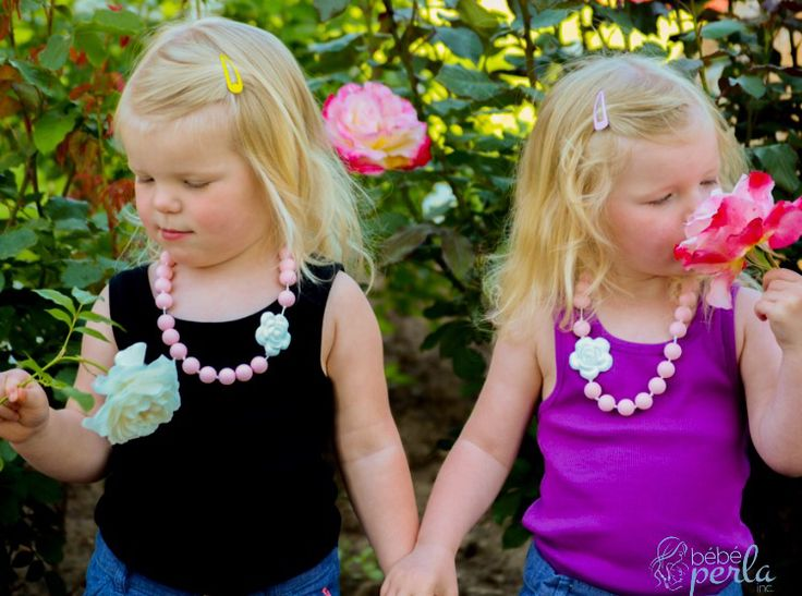 Sometimes you need to just stop and smell the roses. Here are Natalie and Haley modelling their Pink Flora little girl necklaces. Mommy even got a matching necklace! www.bebeperla.com - we can customize too! #twins #twinlove #twingirls #roses #summer #pink #thatsdarling #mommyandme